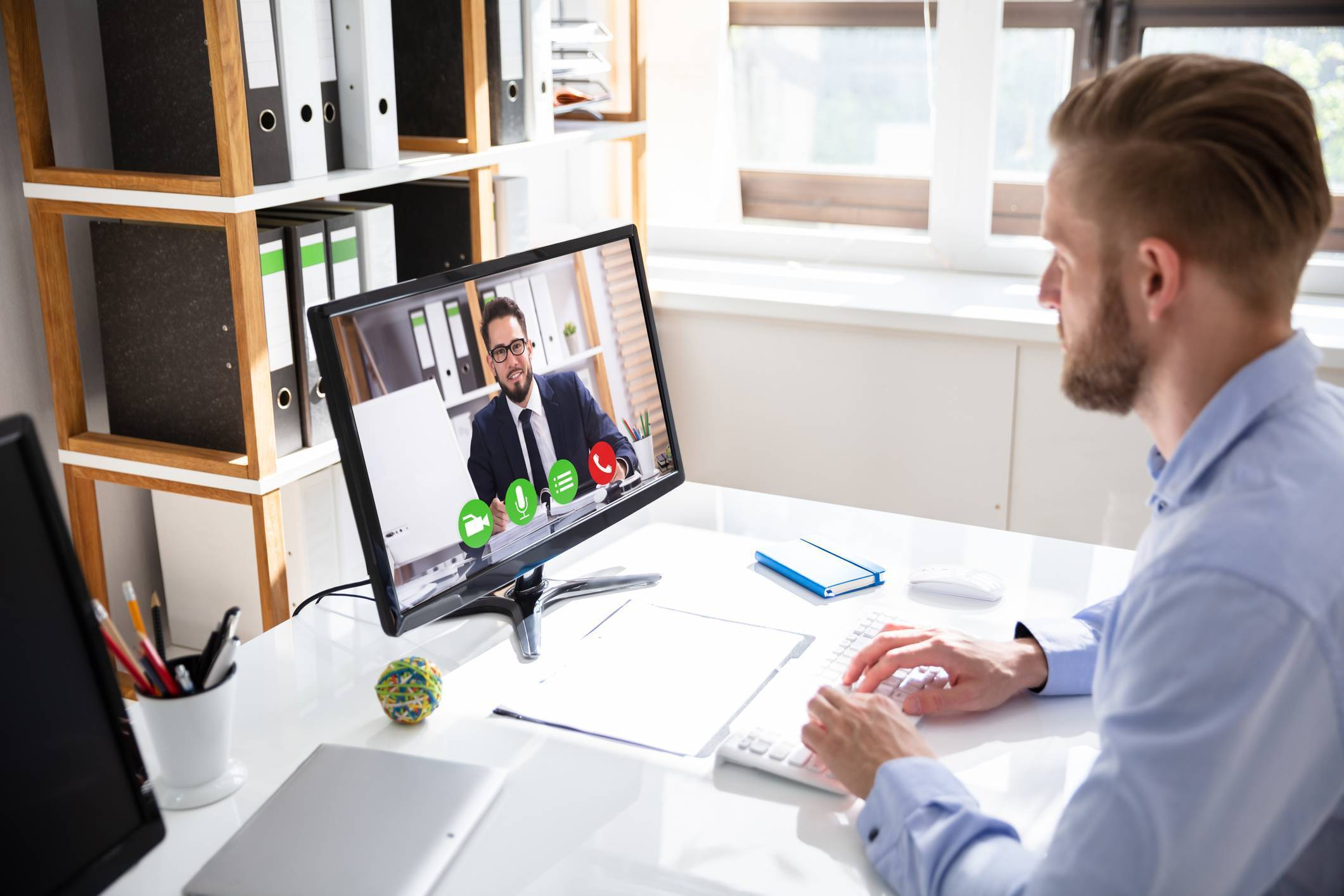 business man video conferencing with sales rep on desktop computer at office desk