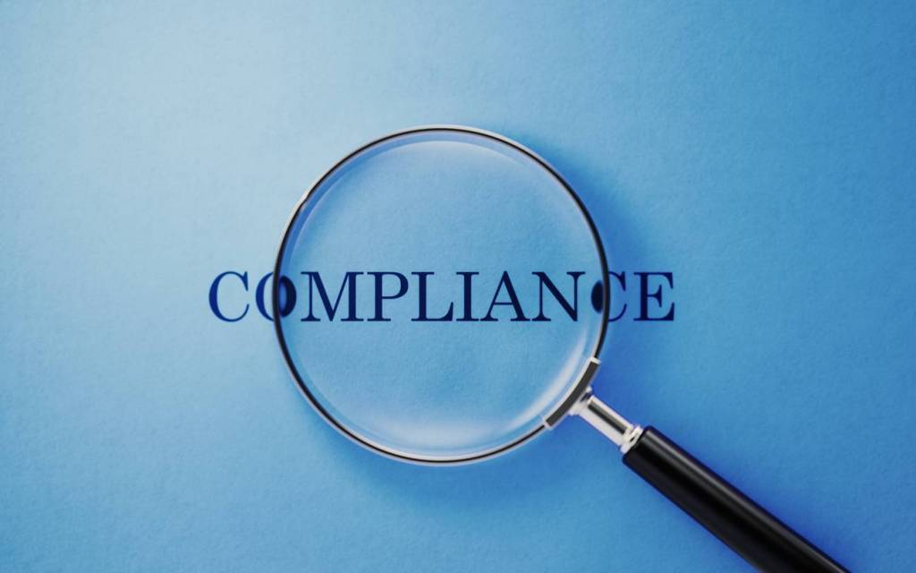 Magnifier and compliance text on blue background